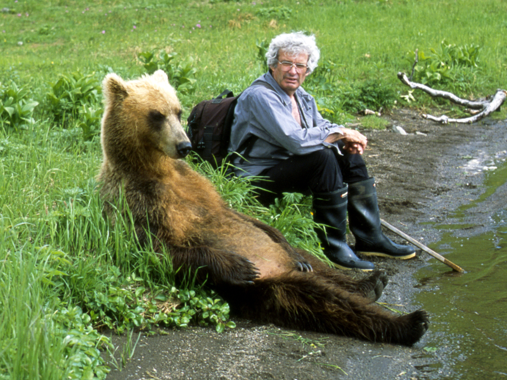 Charlie Russell sitting next to a grizzly bear in Kamchatka. Photo by Maureen Enns Studios Ltd